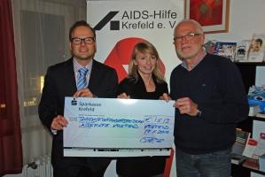 Manuel Kölker (links) übergibt den symbolischen Scheck an Patrizia Helten und Peter Ditz von der Aidshilfe.